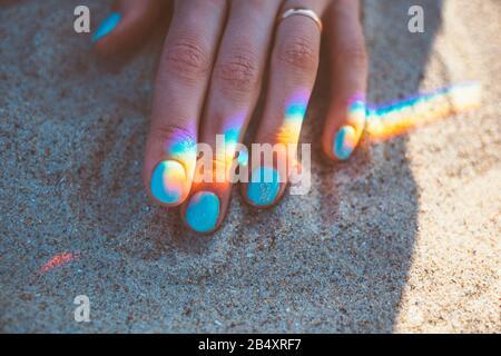 Jeune femme main avec manucure bleue et réflexion de l'arc-en-ciel sur le sable, gros plan. Banque D'Images