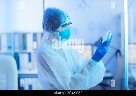 Vue latérale horizontale prise par un scientifique de laboratoire médical non reconnaissable qui tient un plat de Petri avec un spécimen de virus qui le regarde