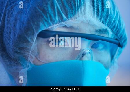Gros plan horizontal extrême d'une femme asiatique non reconnaissable portant un masque de protection, une casquette médicale et des lunettes regardant l'appareil photo