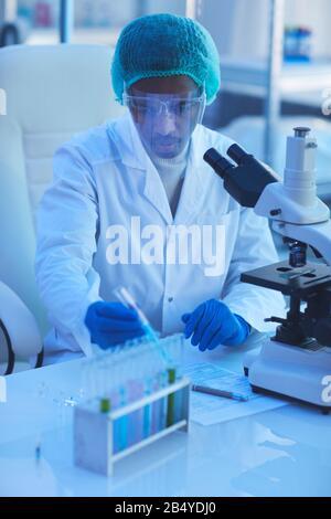 Tir vertical à grand angle de jeune homme africain américain portant un manteau blanc travaillant dans le laboratoire de recherche médicale moderne ivestigating et développement ne