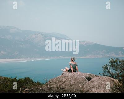 Une jeune femme assise au bord d'un rocher au sommet d'une montagne qui donne sur un magnifique bleu océan