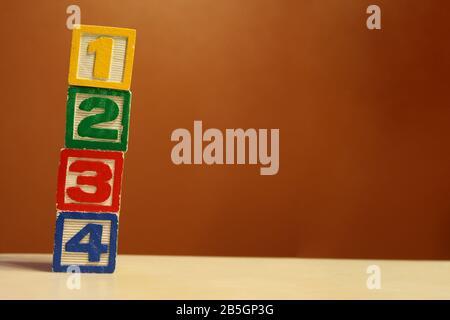 Pile verticale de blocs de jouets en bois de couleur alphabet sur fond orange Banque D'Images