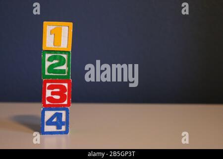 Pile verticale de blocs de jouets en bois de couleur alphabet sur fond bleu Banque D'Images