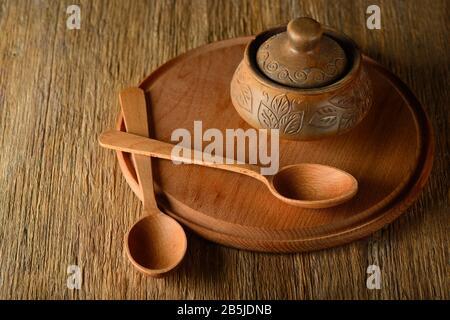 Cuillère en bois, plaque, pot en argile sur la vieille table. Espace de copie Banque D'Images
