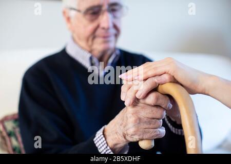 Homme Principal Mécontent Avec Les Mains Sur Le Bâton De Randonnée Étant Réconforté Par Le Visiteur De Santé De Femme Banque D'Images