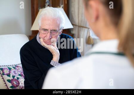 Homme Principal Mécontent Visité Par Une Infirmière Féminine Banque D'Images