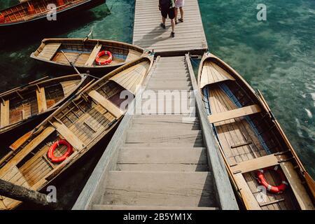 Bateaux en bois attachés à un quai à une station de bateau sur un lac en Italie, le lac Dolomites.Prasser wildsee dans les montagnes dolomites dans le sud du tyrol en Italie Banque D'Images