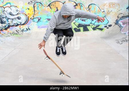 jeune patineuse faisant un tour de saut au skate park . Banque D'Images