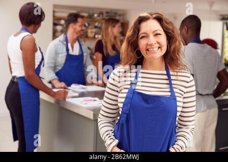 Portrait De Smiling Femme Mûre Portant Tablier Prenant Part À La Classe Cookery Dans La Cuisine Banque D'Images