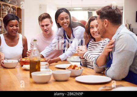 Groupe D'Amis Assis Autour De La Table Manger Repas À La Maison Ensemble Banque D'Images