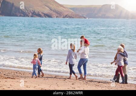 Randonnée En Famille Multi-Génération Le Long De Shoreline Of Beach By Waves Ensemble