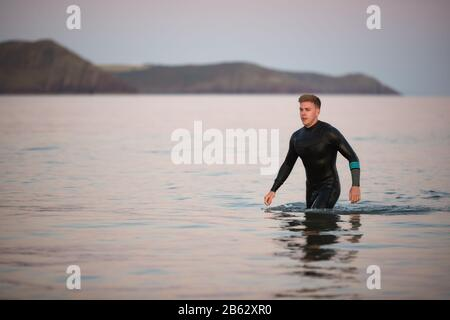 Homme Portant Une Combinaison Humide Traversant La Mer Peu Profonde Par Shore Banque D'Images