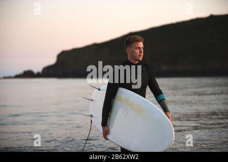 Homme Portant Des Wetsuit Transportant Surfboard LorsQu'Il Sort De La Mer Banque D'Images