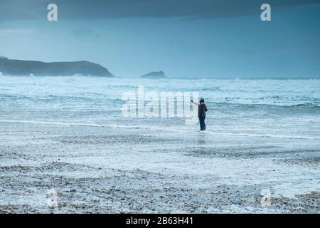 Les touristes utilisant un smartphone pour prendre une photo de selfie dans les conditions climatiques glaciales froides sur la plage de Fistral à Newquay à Cornwall.