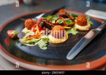 délicieux plat de falafel avec des légumes et de la sauce en arrière-plan du restaurant