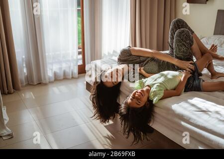 mère et fille asiatiques posée sur le lit quand vous aimez jouer ensemble