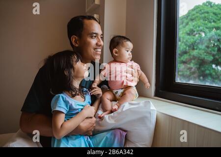 père asiatique et deux petites filles qui sortent de la vitre lorsqu'elles s'assoir sur le lit dans la chambre