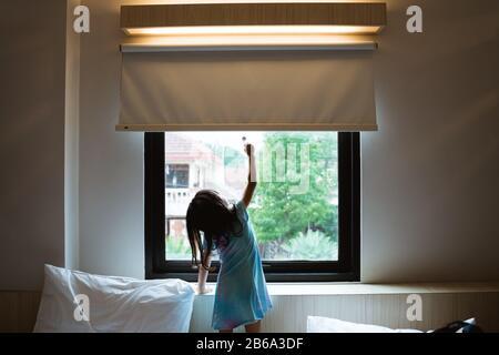 petite fille asiatique atteignant rideau de fenêtre dans la chambre
