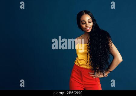 Portrait d'une jeune femme heureuse avec de très longs cheveux bouclés noirs souriants et regardant vers le bas, avec un bras à la taille