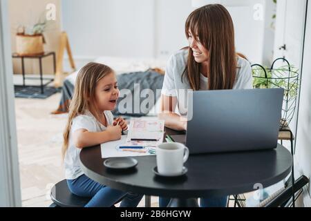 Travailleur indépendant maman sur l'ordinateur portable avec petite fille jouant sur la table ensemble à la maison Banque D'Images