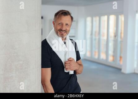 Placez un homme en bonne santé avec une serviette drapée autour du cou en vous penchant contre un pilier dans une salle de sport spacieuse souriant à l'appareil photo Banque D'Images