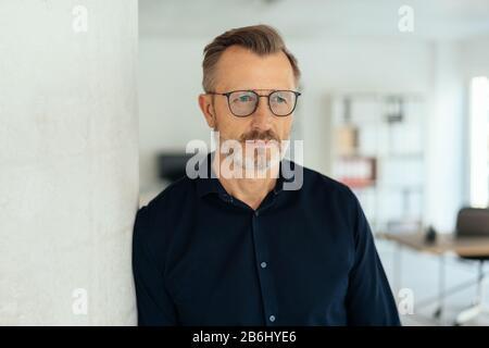 Homme réfléchi avec une expression contemplative se penchant contre un pilier à l'intérieur regardant de côté Banque D'Images