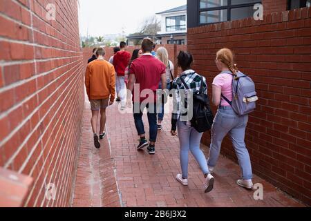 Vue arrière des amis marchant ensemble à l'extérieur Banque D'Images