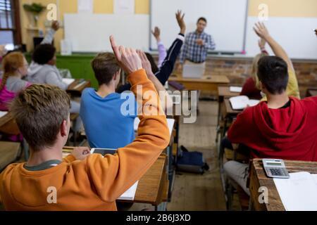 Vue arrière des étudiants levant les mains en classe Banque D'Images