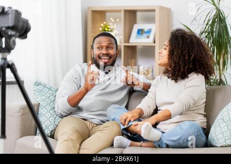 blogging, videoblog et concept de personnes - heureux afro-américain couple de blogueurs vidéo avec caméra videobblogs à la maison Banque D'Images