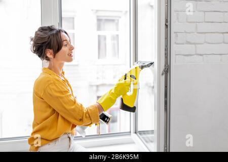 Jeunes femmes laver les fenêtres avec un dispositif de nettoyage spécial à la maison. Concept d'entretien ménager professionnel Banque D'Images