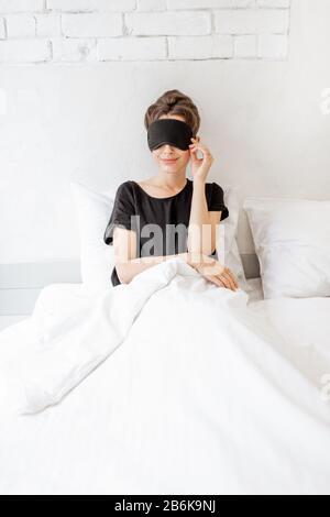 Jeune femme dans le masque de sommeil se réveillant dans la chambre. Concept de Bonjour Banque D'Images