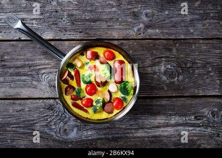 omelette ou frittata cuite au four avec saucisses, brocoli, tomates cerises, fromage fondu dans une poêle sur une table rustique en bois, vue horizontale de dessus, fl Banque D'Images