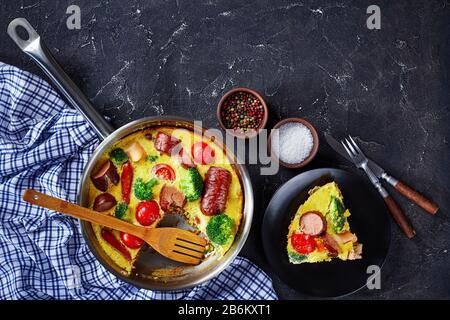 frittata avec saucisses, brocoli, tomates cerises, fromage fondu dans une poêle sur une table en béton et une partie sur une assiette, vue horizontale d'en haut Banque D'Images