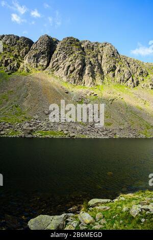 L'eau de chèvre et le Dow Crag dans les collines de Coniston du district du lac anglais; les grimpeurs de roche sont tout simplement perceptibles Banque D'Images