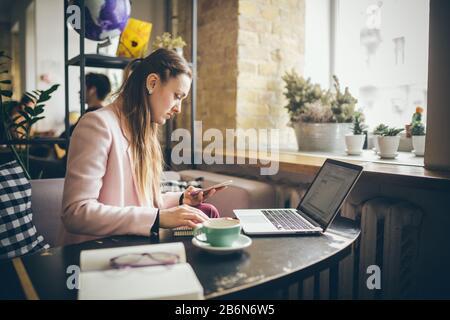 Femme travaillant sur le projet de planification. Copywriter freelance utilisant ordinateur portable, téléphone mobile et Internet, travaillant en ligne, recherche d'informations