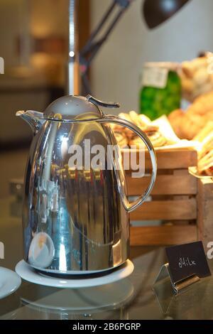 Restauration de boissons chaudes. Bouchon à lait en métal pour le café . Thermos avec eau chaude pour le lait de l'après-midi sur la table en bois dans un hôtel 5 étoiles de luxe. Banque D'Images