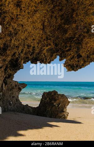 Vue à travers une grotte de corail sur une plage de sable sur Osprey Bay dans le parc national du Cap Range en Australie occidentale. Banque D'Images