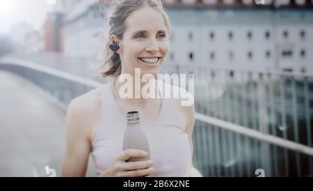 Junge athlétisme Frau nach dem Joggen mit Wasserflache in der Hand.Jeune femme athlétique après le jogging avec bouteille d'eau à la main.