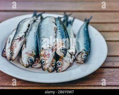 Une plaque de harengs et de sardines prêts sur une table Woden prêt pour la cuisine.