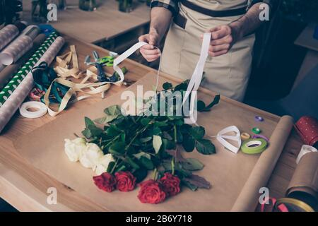 Haut haute angle vue rognée photo de homme gars tenir main prendre le ruban blanc faire assistant surprise serre fleuristry botanique à carreaux chemise