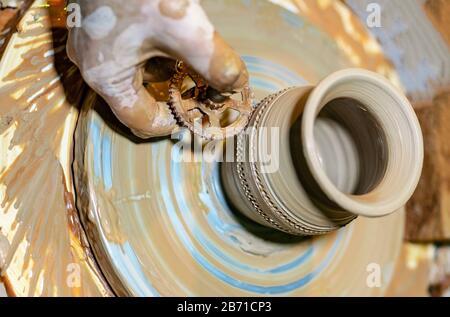 Le potter professionnel fait un pot sur une roue de poterie. Mains d'un potier.