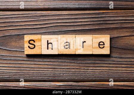 Partager mot écrit sur une cale en bois. partager du texte sur table, concept. Banque D'Images