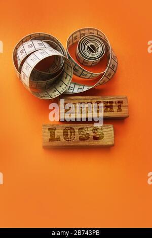 Les mots de perte de poids sur les blocs de bois s'signent avec du ruban de mesure sur fond orange Banque D'Images