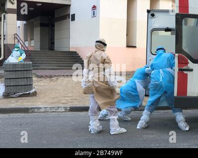 Minsk, Biélorussie. 13 mars 2020. Minsk, BIÉLORUSSIE - 13 MARS 2020: Les membres d'une équipe médicale en costume de protection chargent une civière dans une ambulance en dehors du dortoir no 3 à l'Université d'État biélorusse. Natalia Fedosenko/TASS crédit: ITAR-TASS News Agency/Alay Live News Banque D'Images