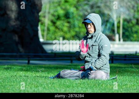 Dublin, Irlande, février 2018 un homme asiatique du Moyen-âge assis et méditant sur une herbe verte dans un parc vert St Stephens, fond flou Banque D'Images