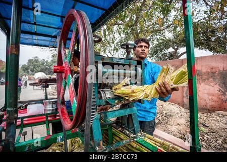 Agra, UTTAR PRADESH, INDE - 24 FÉVRIER 2015 : jeune homme indien qui produit du jus de canne à sucre très célèbre en Inde Banque D'Images