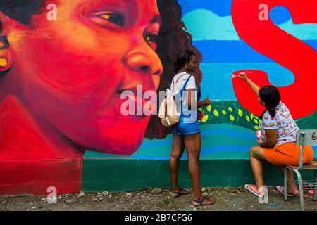Les étudiantes afro-colombiennes peignent une fresque liée à la société et à l'environnement sur un mur scolaire à Quibdó, Colombie. Banque D'Images