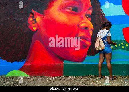 Une étudiante afro-colombienne peint une murale de société et de milieu sur un mur scolaire à Quibdó, en Colombie. Banque D'Images