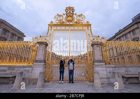 Deux touristes prenant des photos de téléphones cellulaires à travers les bars dorés de la porte du château de Versailles dans la périphérie de Paris, France, Europe Banque D'Images