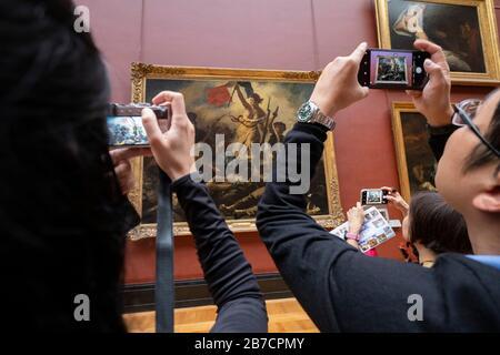 Trois touristes prenant des photos de la liberté à la tête de la peinture populaire par l'artiste Eugene Delacroix au Musée du Louvre à Paris, France, Europe Banque D'Images